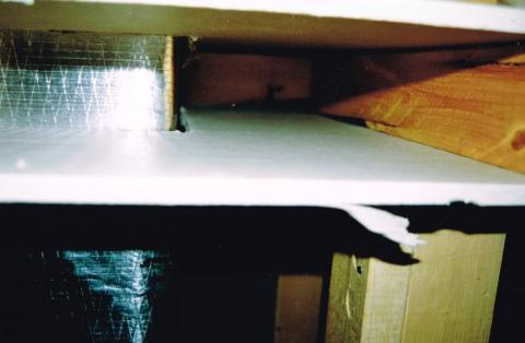 Cut-away view showing unsealed gaps around a heating duct that goes through a wall
