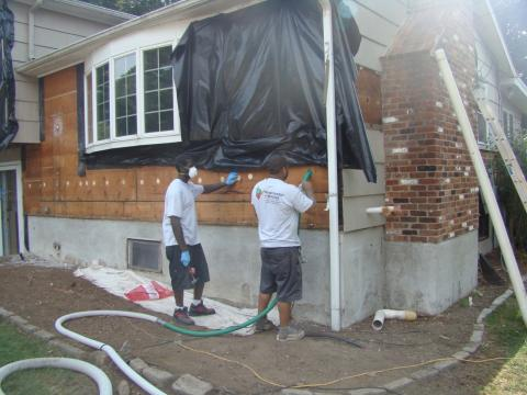 Siding has been removed so cellulose insulation can be dense-packed into the exterior walls of this home