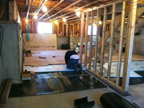 Retrofit of an existing basement slab by adding dimple plastic mat, rigid foam insulation, and a floating subfloor