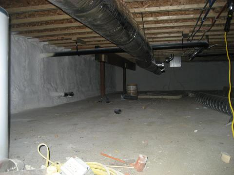 Rigid foam insulation and a thin slab were installed over the dirt and gravel of this sealed crawlspace