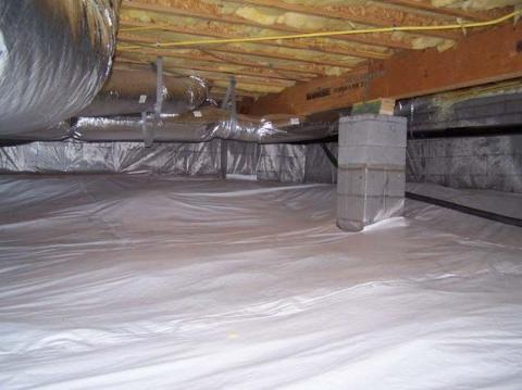Polyethylene completely covers the floor of this crawlspace and is attached to the walls and piers as well