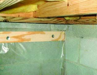 Polyethylene is being attached to the crawlspace floor and walls with plywood furring strips