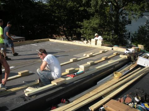 Wood blocking for future PV panel installation is installed in the layers of polyisocyanurate rigid foam insulation during a flat roof retrofit