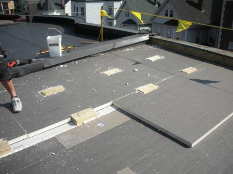 The wood blocking for future PV panel installation extends above the surface of the top layer of polyisocyanurate rigid foam insulation installed as part of a flat roof retrofit