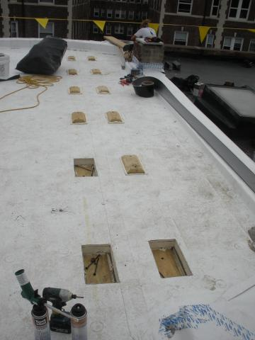 Roofing membrane is installed over polyisocyanurate rigid foam insulation and insulation cover board that has been cut to fit around locations for blocking for the PV system rack