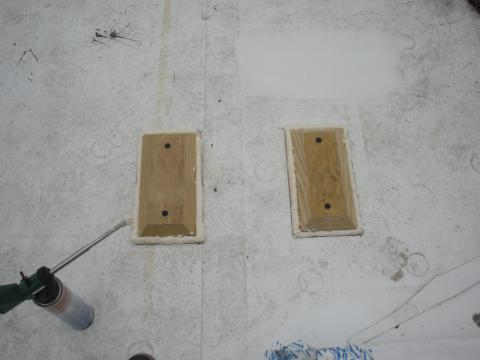 Blocking installed on a flat roof for a PV system rack is sealed around the edges with sealant then will be covered with self-adhering roof membrane to prevent water leakage