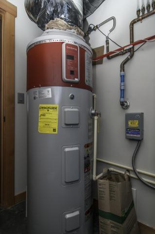 This 80-gallon heat pump water heater is ducted to pull heat from outside air drawn from the south side of the house and to exhaust cooled air outside on the north side of the house to efficiently heat water without impacting interior room temperatures.