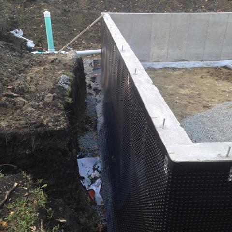 A dimpled rain mat and perforated drain pipe provide drainage around the basement foundation.