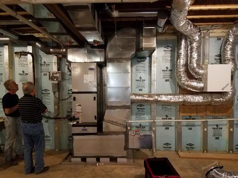 The precast insulated concrete walls of the basement provide a conditioned space for the high-efficiency (18 SEER, 9.5 HSPF) air-source heat pump, with its variable-speed fan, five-stage compressor, and MERV 11 filter.
