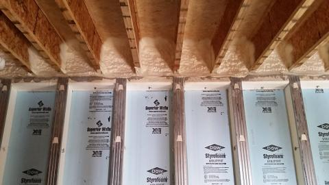 The rim band connecting the insulated precast concrete basement walls to the floor joists above is spray foamed to provide air sealing and insulation in this hard-to-seal juncture.