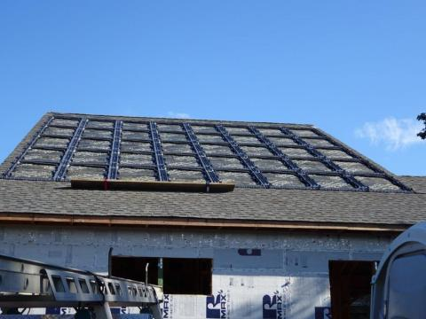 The photovoltaic panels sit in a waterproof plastic tray that was installed directly on the roofing underlayment, then surrounded with roofing shingles.