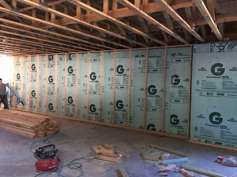 The poured concrete basement walls are insulated along the inside with 2.5 inches of extruded polystyrene insulation.