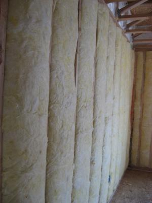 Unfaced fiberglass batt insulation is installed to completely fill the wall cavities and is sliced to fit around wiring, piping, and other obstructions in the wall cavities